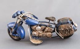 在灰色背景的微型玩具摩托车 免版税图库摄影