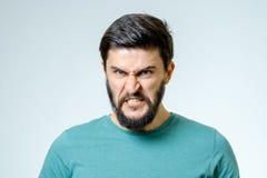 在灰色背景的恼怒和愤怒的男性 免版税库存照片