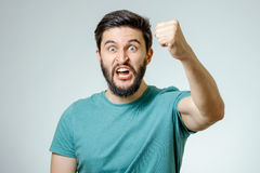 在灰色背景的恼怒和愤怒的男性 免版税库存图片