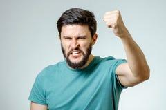 在灰色背景的恼怒和愤怒的男性 库存图片