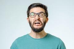 在灰色背景的恼怒和愤怒的男性 库存照片