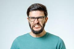 在灰色背景的恼怒和愤怒的男性 免版税图库摄影