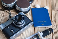 在灰色背景的护照 太阳镜,帽子 在背景的葡萄酒照相机 欧盟签证自由存取 浅景深,焦点 库存照片