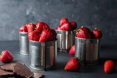 在灰色背景的新鲜的草莓 点心用草莓和巧克力,焦糖 在铁罐的草莓 库存图片