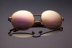 在灰色背景的时髦的被对立的被反映的太阳镜 免版税图库摄影