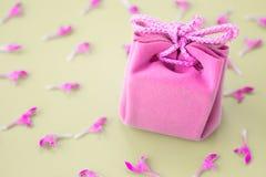 在灰色背景的桃红色礼品券与花 美丽的精美礼物 免版税库存照片