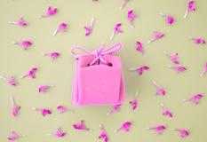 在灰色背景的桃红色礼品券与花 美丽的精美礼物 免版税库存图片