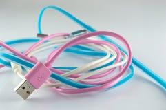在灰色背景的桃红色蓝色和白色USB缆绳 免版税库存图片