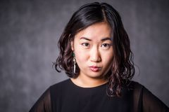 在灰色背景的滑稽的亚洲妇女ina黑色礼服 免版税库存照片