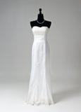 在灰色背景的现代白色婚礼礼服 图库摄影