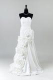 在灰色背景的现代白色婚礼礼服 库存图片