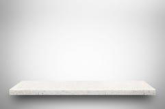 在灰色背景的白色石架子 库存图片