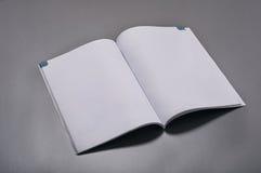 在灰色背景的空白的杂志 库存照片