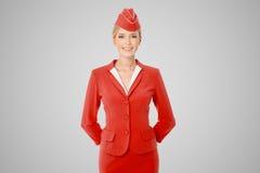 在灰色背景的红色制服打扮的迷人的空中小姐 免版税库存图片