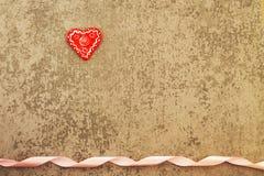在灰色背景的红色心脏与丝带 免版税库存图片