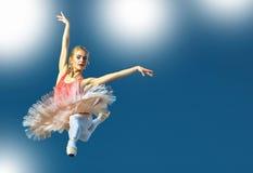 在灰色背景的美丽的女性跳芭蕾舞者 芭蕾舞女演员穿桃红色芭蕾舞短裙和pointe鞋子 免版税库存照片