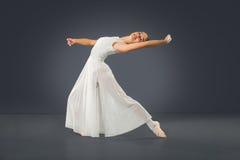 在灰色背景的美丽的女性跳芭蕾舞者 免版税图库摄影