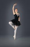 在灰色背景的美丽的女性跳芭蕾舞者 库存照片