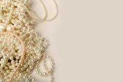 在灰色背景的美丽的奶油色婚礼珍珠项链 图库摄影