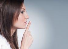 在灰色背景的美好的少妇沈默 免版税库存图片