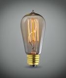 在灰色背景的老电灯泡 免版税库存图片