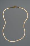 在灰色背景的豪华金黄项链 免版税图库摄影