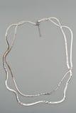 在灰色背景的豪华银色项链 免版税图库摄影