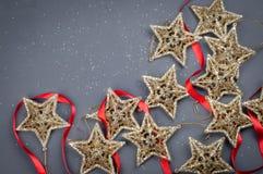在灰色背景的金黄星圣诞节构成装饰与红色丝带 图库摄影