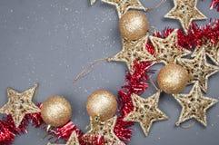 在灰色背景的金黄星圣诞节构成装饰与红色闪亮金属片 免版税库存照片