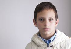 在灰色背景的青春期前的男孩纵向 库存照片