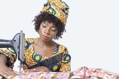 在灰色背景的非裔美国人的女性时装设计师缝合的织品 库存图片