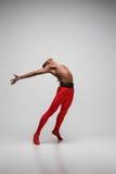 在灰色背景的年轻和时髦的现代跳芭蕾舞者 免版税图库摄影