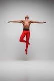 在灰色背景的年轻和时髦的现代跳芭蕾舞者 库存图片