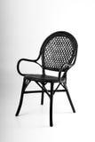 在灰色背景的黑藤椅 库存照片
