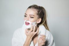 在灰色背景隔绝的白色浴巾的快乐的白肤金发的妇女 获得可爱的女孩应用润湿的奶油的乐趣 免版税图库摄影