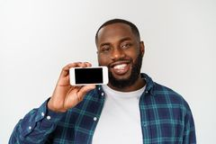 在灰色背景隔绝的英俊的非洲人,提出智能手机和指向与手指空白的黑屏幕 免版税库存照片