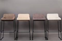 在灰色背景隔绝的四把现代酒吧椅子行  家具系列 库存图片