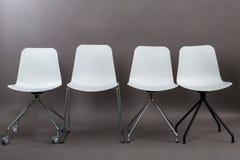 在灰色背景隔绝的四把白色塑料椅子行  家具系列 免版税库存照片