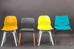 在灰色背景隔绝的四把颜色塑料椅子行  家具系列 免版税库存照片