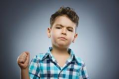 在灰色背景隔绝的恼怒的男孩 他举他的拳头对罢工 特写镜头 库存照片