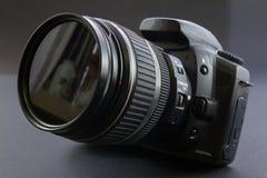 在灰色背景,前面的一台黑DSLR照相机举起 免版税库存图片