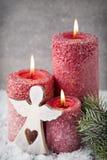 在灰色背景,圣诞节装饰的三个红色蜡烛 免版税库存图片