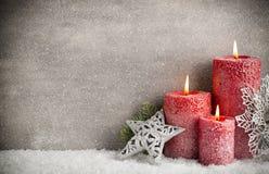 在灰色背景,圣诞节装饰的三个红色蜡烛 Adve 免版税库存照片