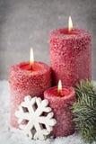 在灰色背景,圣诞节装饰的三个红色蜡烛 Adve 免版税库存图片