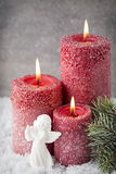 在灰色背景,圣诞节装饰的三个红色蜡烛 Adve 库存图片