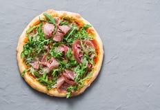 在灰色背景,顶视图的熏火腿自创薄饼 可口开胃菜,快餐,在地中海样式的塔帕纤维布 免版税库存图片