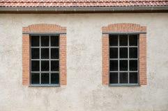 在灰色膏药墙壁上的两个窗口 免版税库存图片