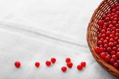 在灰色袋子背景的五颜六色的红浆果 在一个棕色篮子的有机,新鲜和土气红浆果 素食成份 库存照片