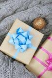在灰色被编织的背景的圣诞节礼物 图库摄影
