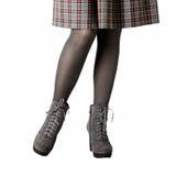在灰色裤袜,一条裙子的女性腿在笼子和在灰色起诉 图库摄影